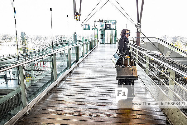 Woman standing with luggage in a train station; Avignon  Provence Alpes Cote d'Azur  France
