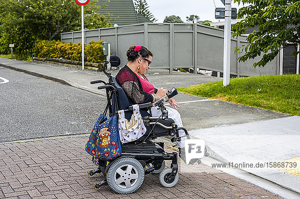Maori woman with Cerebral Palsy in a wheelchair crossing a street; Wellington  New Zealand