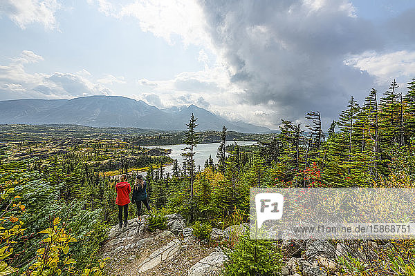 Two women stand on a rock overlooking the landscape of Wright Pass near the Canada/USA border; Yukon  Canada