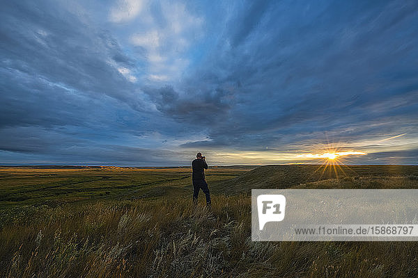 Person taking a photo of the sunrise in Grasslands National Park; Saskatchewan  Canada