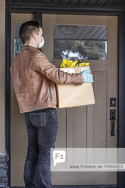 A young man standing with a box of groceries at the door of a house during the Covid-19 World Pandemic; Edmonton  Alberta  Canada
