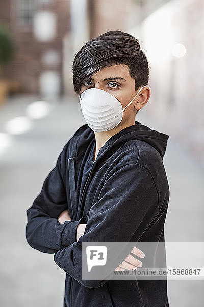 Pre-teen boy stands wearing a protective mask to protect against COVID-19 during the Coronavirus World Pandemic; Toronto  Ontario  Canada