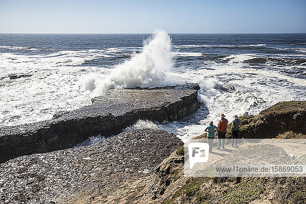 Three people standing on a bluff look down at waves crashing into the rocks below at Wilder Ranch State Park; California  United States of America
