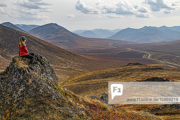Woman exploring the mountains along the Dempster Highway during autumn in the autumn; Yukon  Canada