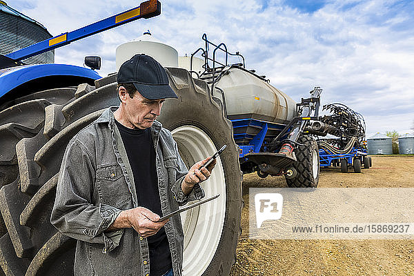 Farmer using a smart phone and tablet while standing on a farm beside equipment; Alberta  Canada