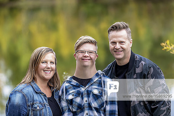 A young man with Down Syndrome posing for a family portrait with his father and mother while enjoying each other's company in a city park on a warm fall evening: Edmonton  Alberta  Canada