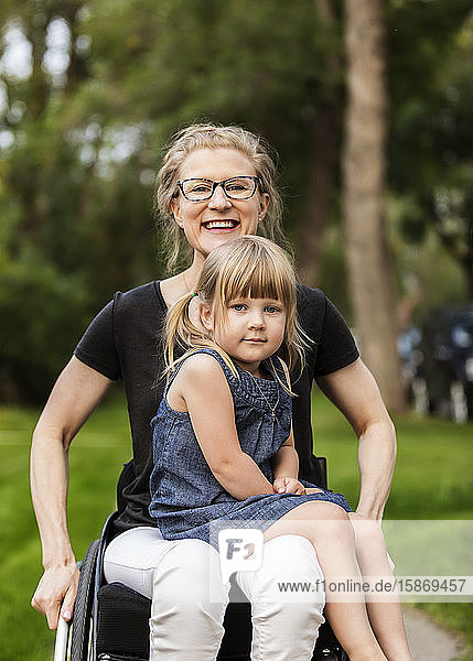 A paraplegic mom holding her little girl in her lap while sitting in her wheelchair in her front yard on a warm summer afternoon: Edmonton  Alberta  Canada.