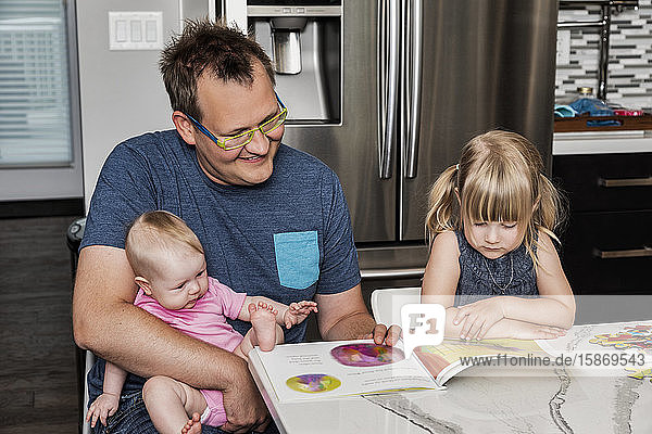 A father sitting down with his daughter in the kitchen to read a book and build a puzzle while holding his baby in his lap: Edmonton  Alberta  Canada