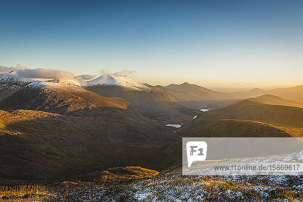 Man with arms outstretched on side of mountain overlooking a valley and snow-covered mountains in Killarney National Park t sunrise; County Kerry  Ireland