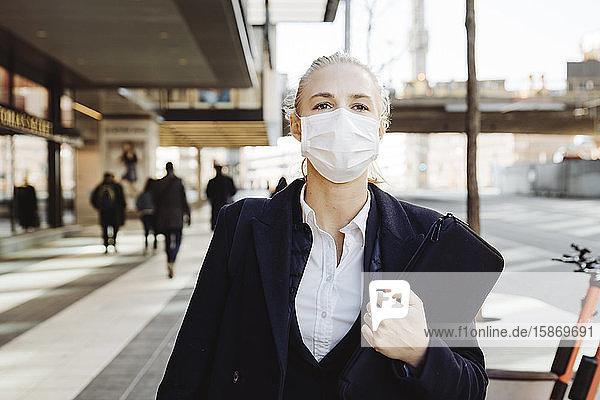 Geschäftsfrau mit Gesichtsmaske auf der Straße
