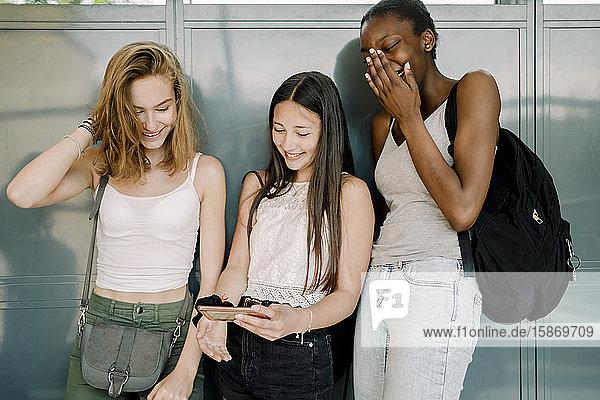 Lächelnde Junior-High-Schüler mit einem Freund  der ein Mobiltelefon benutzt  während er im Schulkorridor steht