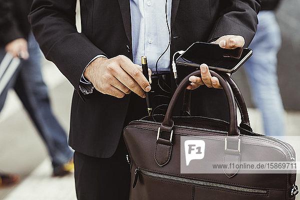 Mittelteil eines männlichen Geschäftsmannes  der einen Stift in eine Tasche steckt  während er im Freien steht