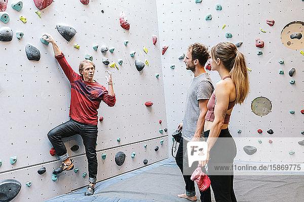 Ausgereifter Ausbilder  der die Schüler im Fitnessstudio über das Bouldern unterrichtet