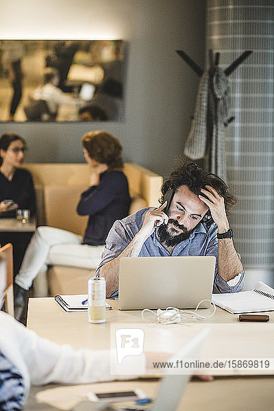 Junger Geschäftsmann spricht mit einem Smartphone  während er im Büro am Laptop arbeitet