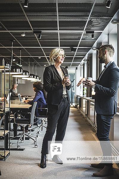 Leitende Geschäftsfrau diskutiert im Amt mit männlichem Mitarbeiter