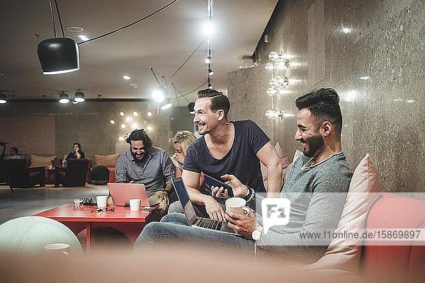 Lächelnde Geschäftskollegen  die über einen Laptop arbeiten  während sie im Kreativbüro sitzen