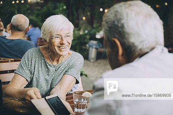 Lächelnde Frau zeigt einem älteren Mann ihr Handy  während sie in einem Restaurant in der Stadt sitzt