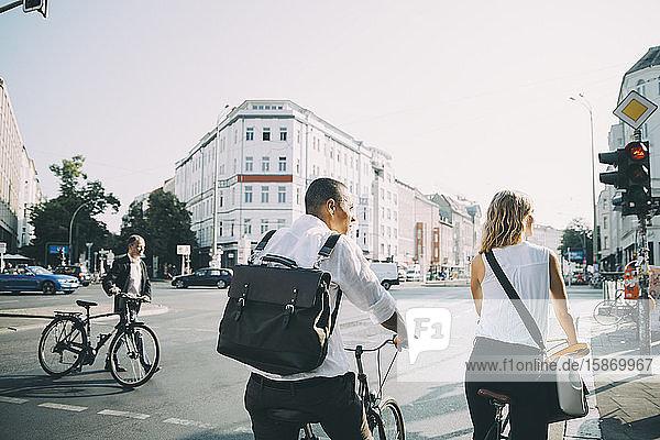 Rückansicht von männlichen und weiblichen Kollegen  die mit dem Fahrrad auf der Straße in der Stadt stehen