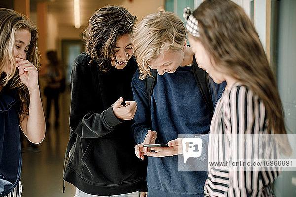 Lächelnde männliche Schüler  die ein Smartphone benutzen  während sie im Schulkorridor bei Freundinnen stehen