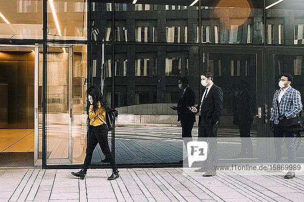 Geschäftsleute mit Gesichtsmasken stehen in der Schlange vor dem Bürogebäude