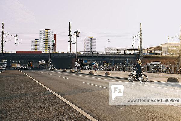 Seltener Anblick einer Geschäftsfrau  die auf der Straße in der Stadt mit dem Fahrrad gegen den Himmel fährt