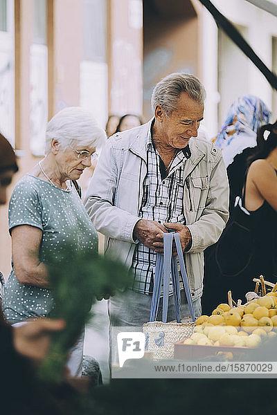 Älteres Touristenpaar kauft Zitronen auf einem Straßenmarkt in der Stadt