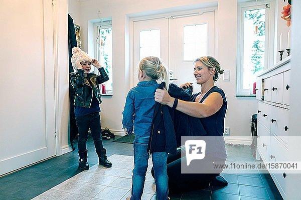 Lächelnde Mutter hilft Tochter mit Jacke  während sie zu Hause kniet