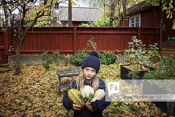 Porträt eines Mädchens  das im Garten frisches Gemüse hält