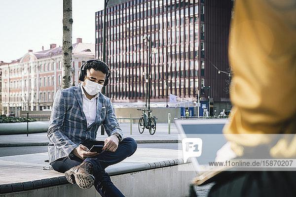 Geschäftsmann mit Gesichtsmaske sitzt draußen und benutzt ein Smartphone