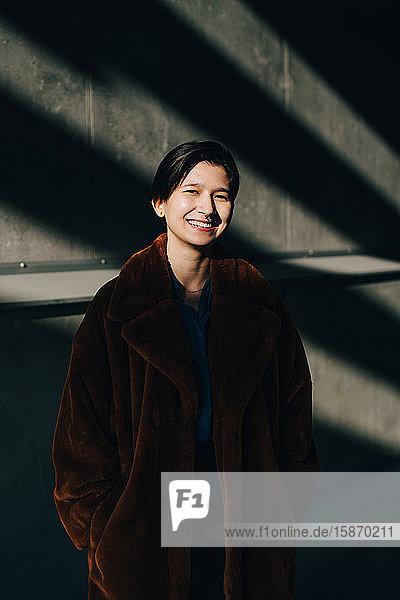 Porträt einer glücklichen jungen Frau an der Wand stehend