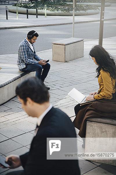 Drei Personen arbeiten auf dem Platz sitzend im Abstand