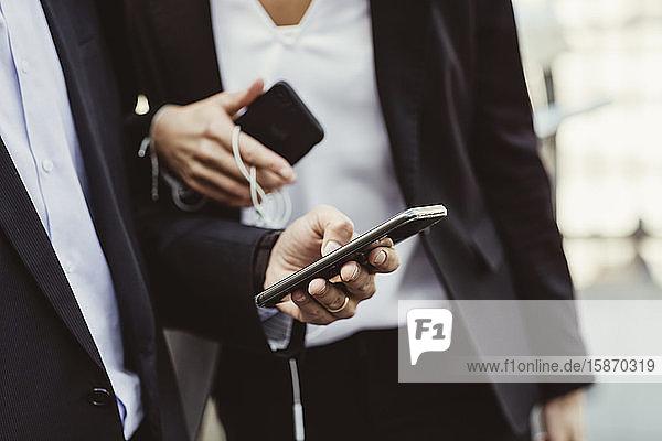 Ein Teil der Geschäftsleute benutzt ein Smartphone  während er mit einer Kollegin im Freien steht