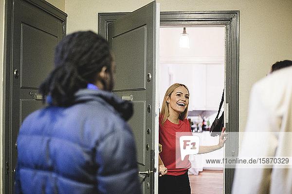 Fröhliche Frau begrüßt Freunde  während sie an der Tür steht