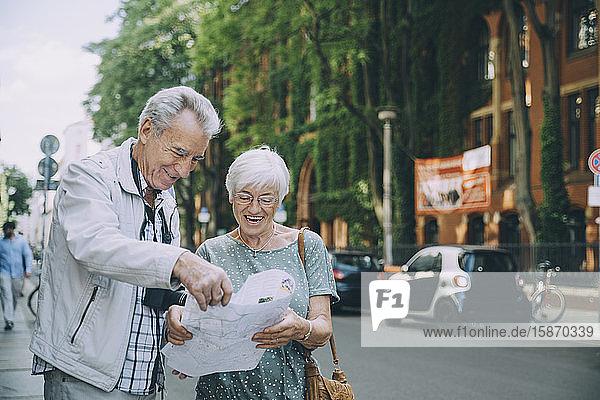 Lächelndes älteres Paar liest Karte  während es im Urlaub auf dem Bürgersteig in der Stadt steht