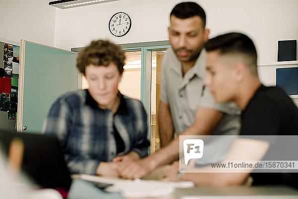Männlicher Lehrer diskutiert mit männlichen Schülern im Stehen im Klassenzimmer