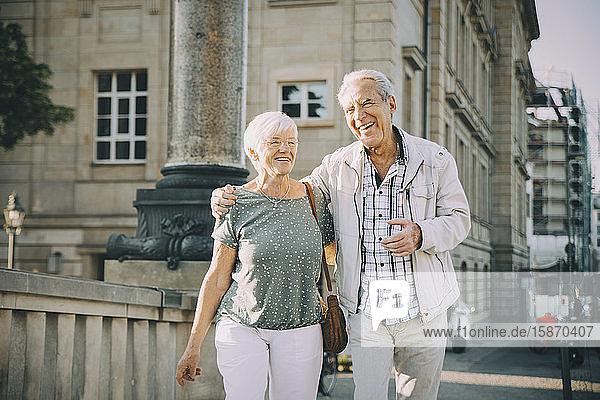Lächelnder Arm eines älteren Mannes  der an einem sonnigen Tag mit einer Frau in der Stadt spazieren geht