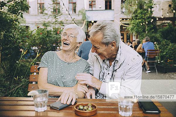 Lächelndes älteres Touristenpaar sitzt im Restaurant in der Stadt