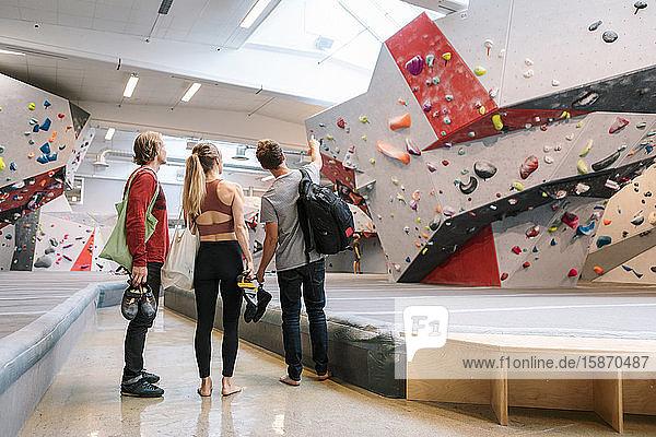 Rückansicht eines Mannes  der auf die Wand zeigt  während er bei der Frau und dem Trainer in der Turnhalle steht