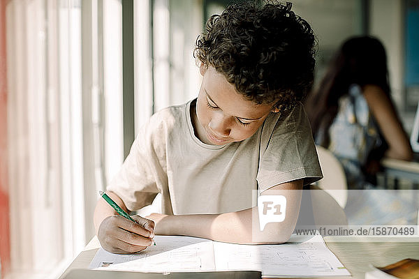 Männlicher Student schreibt  während er im Klassenzimmer sitzt