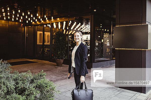 Porträt einer Unternehmerin mit Tasche am Gebäudeeingang stehend