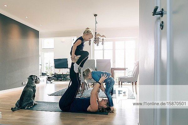 Lächelnde Mutter hebt glückliche Töchter hoch,  während sie zu Hause auf einer Sportmatte liegt