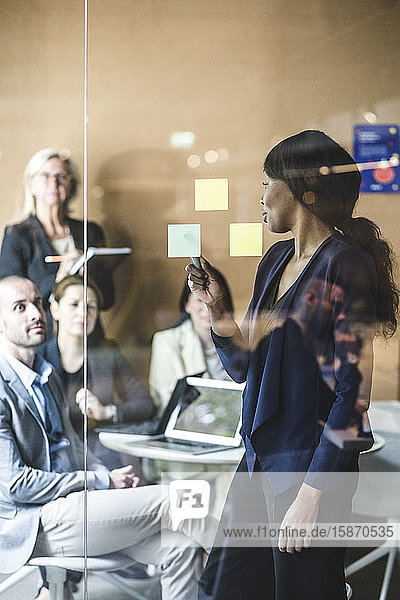 Geschäftsfrau erläutert Notizen mit Kollegen im Sitzungssaal während der Sitzung