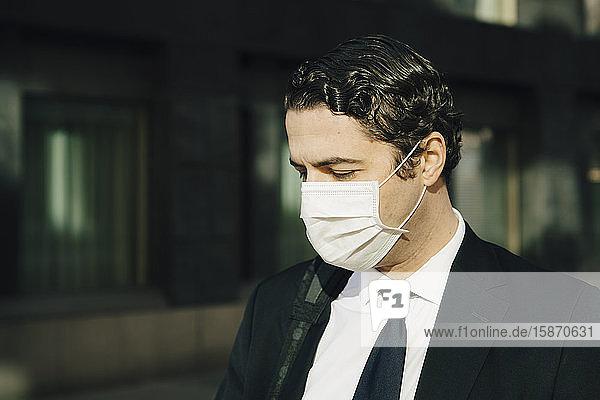 Geschäftsmann mit Gesichtsmaske mit Blick nach unten