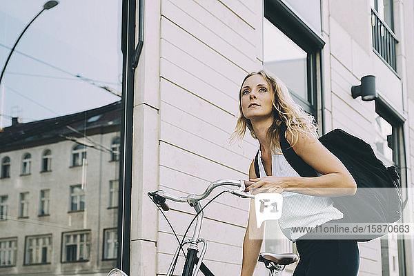 Weibliche Führungskraft mit Fahrrad steht gegen Gebäude in der Stadt
