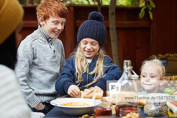 Girl cutting bread while standing by siblings at table for garden party