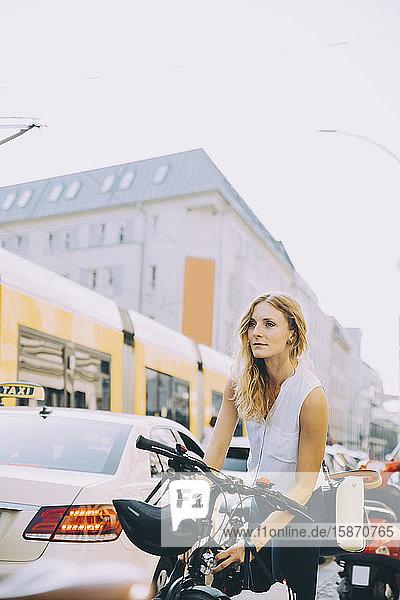 Junge Geschäftsfrau sperrt Fahrrad auf Straße in Stadt gegen Himmel