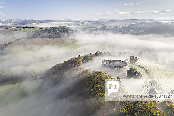 Aerial view by drone of autumn mist swirling above Restormel Castle in Cornwall  United Kingdom  Europe