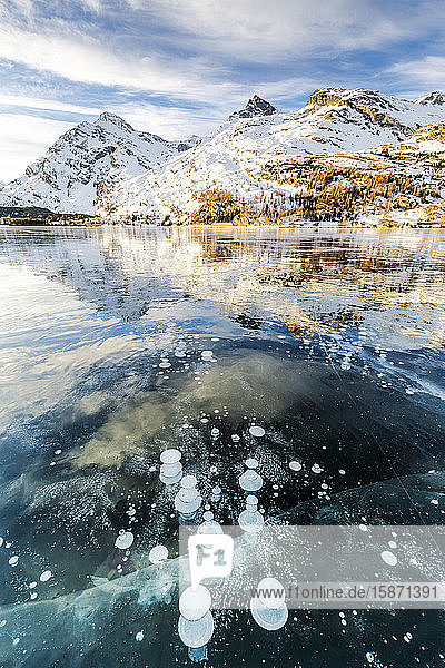 Methane bubbles in the icy surface of Silsersee with snowy peak  Lake Sils  Engadine Valley  Graubunden  Swiss Alps  Switzerland  Europe
