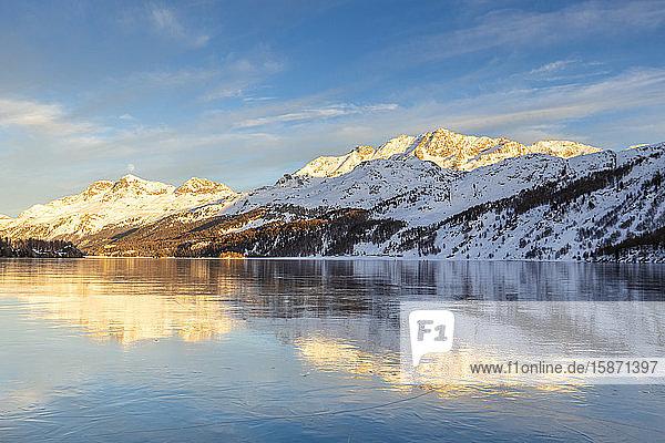Mountains illuminated by sun at sunset reflected on the icy surfaces of Lake Sils  Engadine  Graubunden  Switzerland  Europe