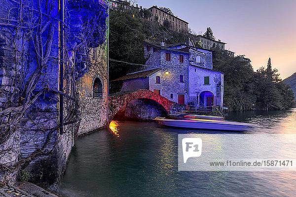 Boat in motion under the illuminated Nesso bridge  Lake Como  Lombardy  Italian Lakes  Italy  Europe